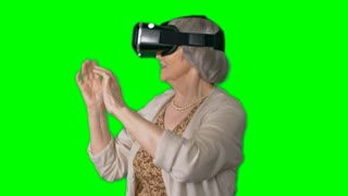 Smiling senior woman wearing virtual reality headset elegantly waving her arms in air and looking around against green screen background
