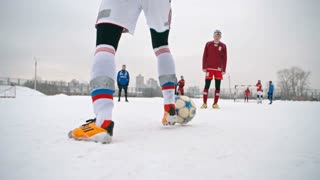 Soccer player handling a ball, getting around opposing players and unsuccessfully attempting taking a shot on goal during a play on snow-covered winter field