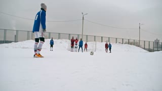 Soccer player taking a free kick in winter match, goalkeeper making a save