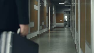 Static camera view of businessman walking away along the business center corridor