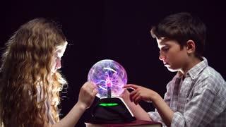 Static shot of kids gazing at magic ball in profile