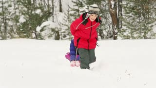 Strong kid pushing his sister sitting on a sled through the winter forest