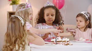 Sweet little princesses eating strawberries and whipped cream from top of birthday cake