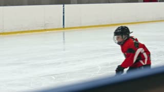 Talented little hockey player pushing the puck into the net of opposing team in slow moti