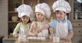 Team of charming little cooks cracking eggs into bowl