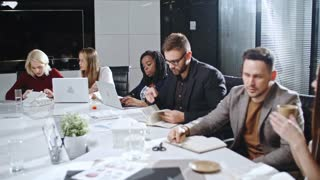 Team of company executives sitting in meeting room and working together at table with documents and laptops on it