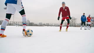 Teenage athletes playing soccer on snow-covered winter field: forward getting around opposing defenders and attempting to take a shot on goal
