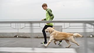 Teenage boy in sportswear jogging with trained golden retriever outdoors at cold autumn day in slow motion