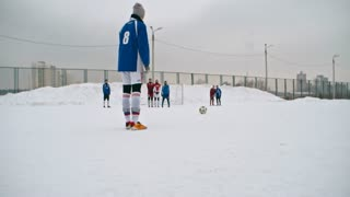 Teenage soccer player scoring a free kick in winter match