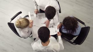 The above view of an executive team reviewing a blueprint