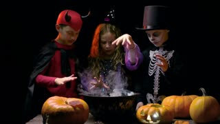 Three children dressed for Halloween celebration making potion