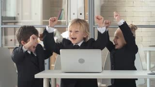 Three little business kids putting their hands up and shouting out with joy in the office