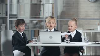 Three little children in business suits sitting at table with laptop on it launching paper planes looking happy.