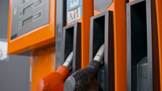 Tilt down closeup shot of female hand putting back fuelling nozzle at gas pump