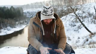 Tilt down of man sitting by fire on camping trip in winter rubbing his cold hands together and trying to warm up