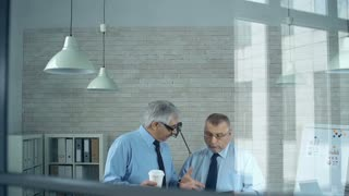 Tilt down the office behind the window with two men discussing business