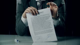 Tilt up of businessman at the office desk tearing the contract apart
