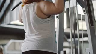 Tilt up of fat woman hanging on bar and doing pull-up exercises in the gym