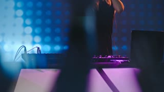 Tilt up of female blond DJ jumping and dancing behind decks in nightclub, LED video wall in background