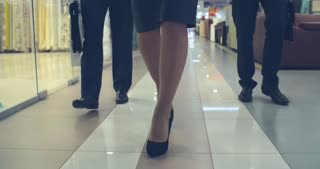 Tilt up of female business leader holding laptop and walking with two businessmen through corridor in shopping mall