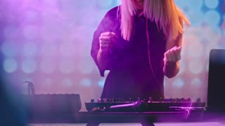 Tilt up of seductive female DJ with blond hair dancing behind decks and singing at party in nightclub