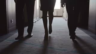 Tilt up of two businessmen and businesswoman walking through dark corridor in hotel in slow motion; one man holding eyeglasses