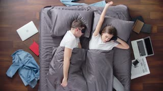Time lapse of young couple waking up in their bedroom, using their laptops, drinking tea, talking and reading newspaper