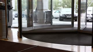Timelapse of people going in and out of the mall through a turning door