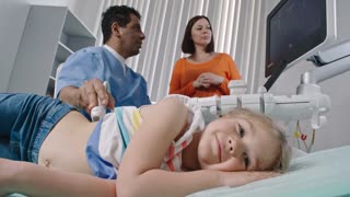 Tired little girl lying on examination bed and looking at camera as Latin-American doctor talking with her mother and performing ultrasound