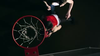Top view of basketball player trying to prevent his opponent while he throwing ball and then it bumping into backboard and falling through net in slow motion in the dark court