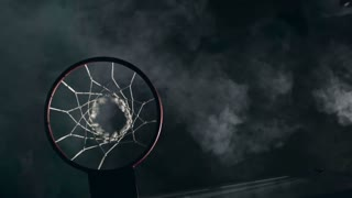 Top view of two basketball opponents jumping in the air and one man slamming ball in the net in the dark court with smoke in slow motion