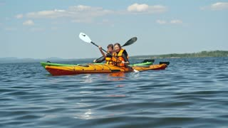 Tracking of couple paddling kayaks together on blue lake surface on sunny summer day