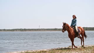 Tracking of elegant smiling woman with her hair flying wildly galloping on her horse along lake