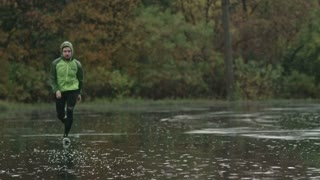 Tracking shot of young sportsman running towards the camera through puddles. Slow motion footage