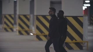 Tracking with backlit of assertive mafia men in black suits with case and sunglasses walking towards waiting man and showing him money in underground parking lot