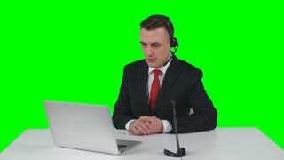 TV commentator sitting at desk in studio with headset and microphone, looking at his laptop and telling news at the camera on green screen background