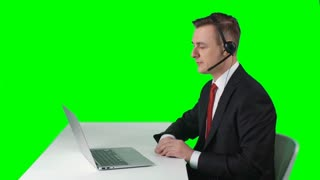 TV reporter sitting at desk in front of laptop, looking at screen and talking. Then putting off headset, looking at camera and telling breaking news on green screen background