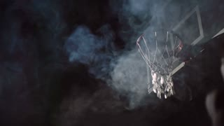 Two basketball players jumping up and one of them performing reverse dunk in slow motion with smoke in the air