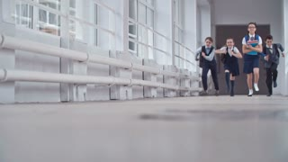Two boys and two girls in school uniform running in slow motion on floor of corridor