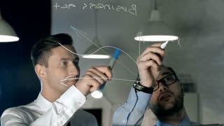 Two businessmen in formal shirts and ties standing behind clear glass dry-erase board in lamp-lit office drawing function graph and numbers and discussing results