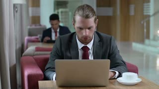 Two businessmen sitting at separate tables in lounge and using digital devices