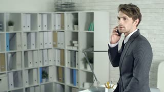 Two businessmen talking in office interrupted by a phone call