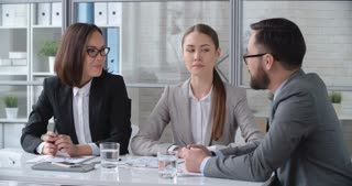 Two businesswoman discussing financial documents with their male partner at the meeting table