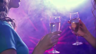 Two girls drinking champagne in the club and dancing seductively