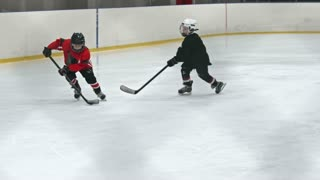 Two kids playing hockey on ice rink: one boy in red uniform handling puck and shooting it into the net