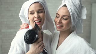 Two ladies in bathrobes singing songs and using hairdryer instead of a microphone