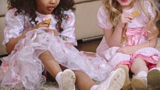 Two little girl dressed like princesses sitting on the floor at home and eating cookies