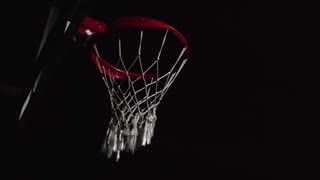 Two professional basketball players jumping in the air and one of them slamming ball in the rim in slow motion in the dark court