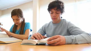 Two pupils reading textbooks in classroom then looking at camera