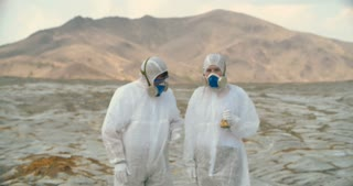 Two shocked scientists in protective coveralls and masks collecting samples in infected zone